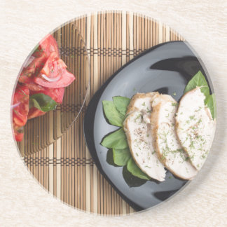 Сhicken meat decorated with basil and tomato salad drink coaster