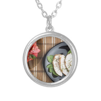 Сhicken meat decorated with basil and tomato salad silver plated necklace