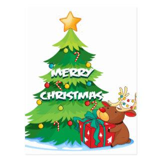 A big christmas tree beside the reindeer hugging t postcard