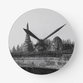 A black and white image of an old temple. round clock