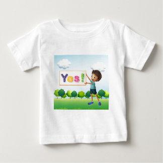 A boy holding a signboard shirts