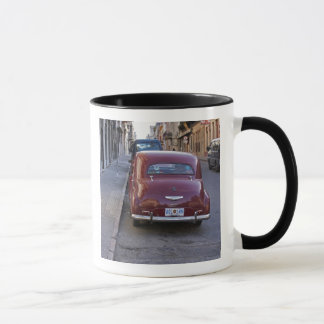 A classic old red Peugeot car parked on a street Mug