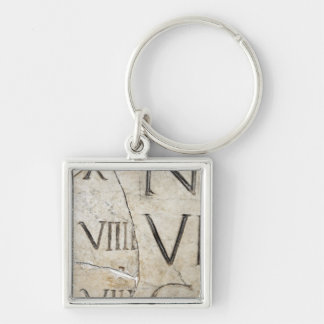A close-up of ancient Roman letters on marble. Keychain