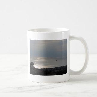 A cloudy sea and a setting sun mugs