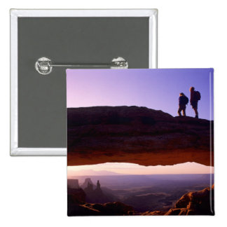 A couple watches sunrise from atop Mesa Arch in Pins