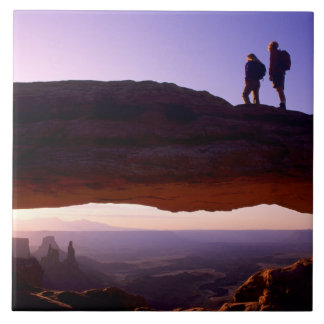 A couple watches sunrise from atop Mesa Arch in Large Square Tile