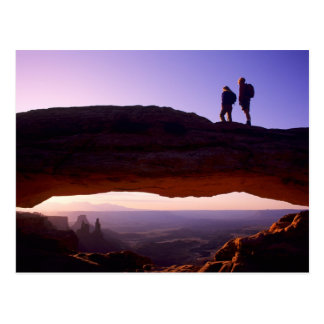 A couple watches sunrise from atop Mesa Arch in Postcard