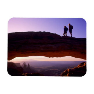 A couple watches sunrise from atop Mesa Arch in Rectangular Photo Magnet