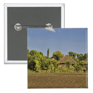 A farmed field in front of thatched roof houses 15 cm square badge