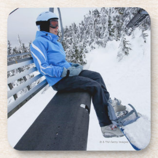 A female snowboarder rides the chair lift in New Beverage Coasters