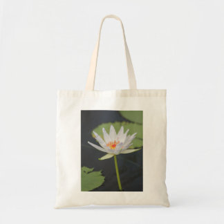 A flower blooming in a pool. tote bag