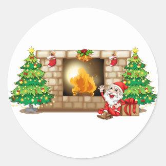 A happy Santa near the fireplace Round Sticker
