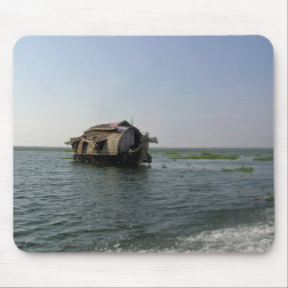 A houseboat moving placidly through a coastal lake mouse pad