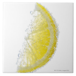 A juicy ripe organic lemon wedge fruit submerged ceramic tile