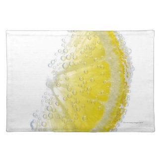 A juicy ripe organic lemon wedge fruit submerged placemat