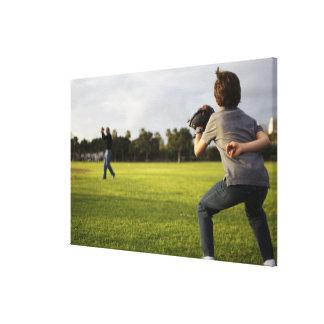 A kid wearing a baseball glove waits for his dad canvas print