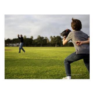 A kid wearing a baseball glove waits for his dad postcard