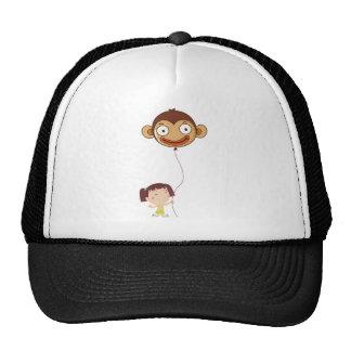 A little girl holding a monkey balloon trucker hat