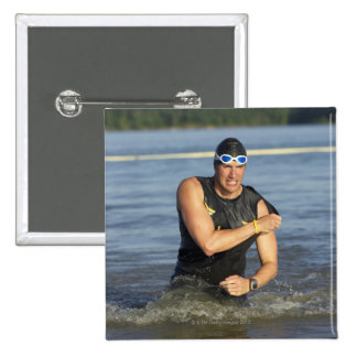 A male athelete running out of the water while 15 cm square badge