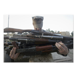 A marine readies 80 pounds of enemy rifles seiz art photo