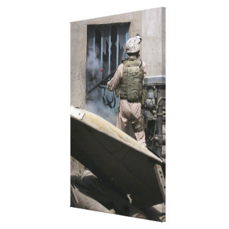 A military policeman uses a breaching round stretched canvas print