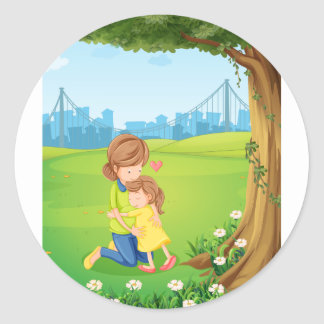 A mother hugging her daughter under the tree classic round sticker
