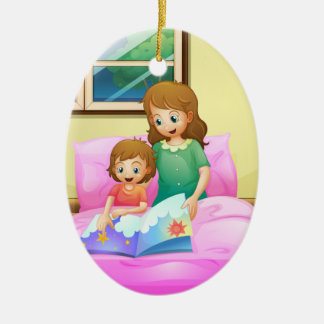 A mother reading with her daughter ceramic ornament