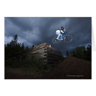 A mountain biker jumps off a log cabin in Idaho. Greeting Card