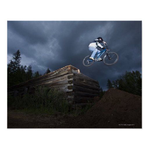 A mountain biker jumps off a log cabin in Idaho. Posters