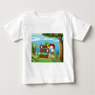 A parrot and a girl beside a signboard in the fore tee shirt