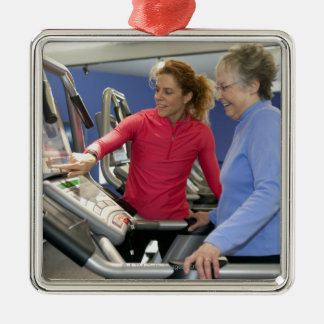 A personal trainer helps a senior woman on a christmas tree ornaments