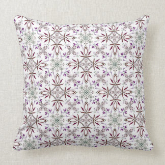 A repeating pattern of leaves, vines and swirls cushion