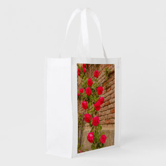 a roses climb on a brick wall on reusable bag