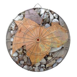 a rusty leaf on pebbles dartboard