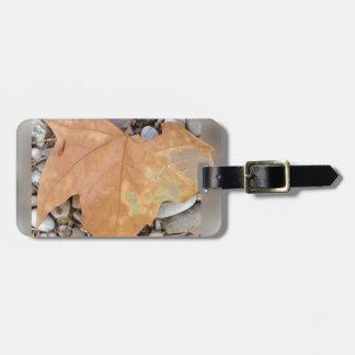 a rusty leaf on pebbles luggage tag
