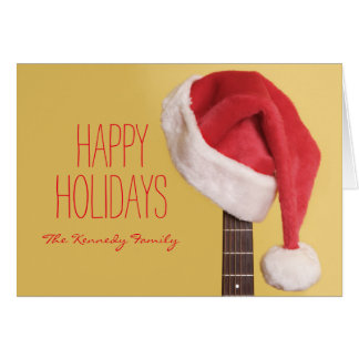 A Santa hat hangs on an acoustic guitar in front Card