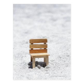A small chair in the sandy beach postcard