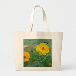 A small dragon fly sitting on a yellow flower canvas bag