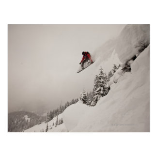 A snowboarder jumps off a cliff into powder in postcard