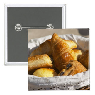 A wicker breakfast basket with croissants and pinback buttons