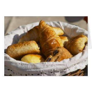 A wicker breakfast basket with croissants, and cards