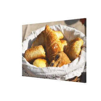 A wicker breakfast basket with croissants, and gallery wrapped canvas