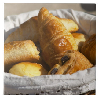 A wicker breakfast basket with croissants, and large square tile