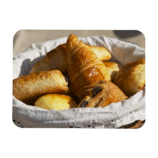 A wicker breakfast basket with croissants and vinyl magnet