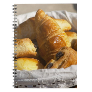 A wicker breakfast basket with croissants, and spiral note books