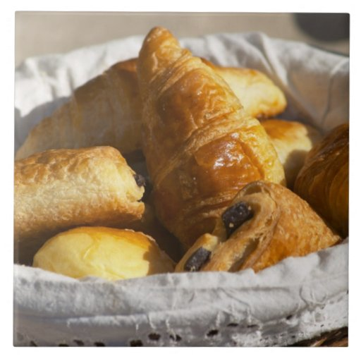 A wicker breakfast basket with croissants, and ceramic tile
