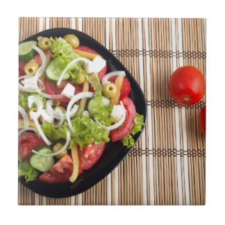 Aerial view of one portion of vegetable salad small square tile