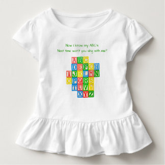 Alphabet blocks on a toddler's dress