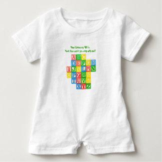 Alphabet blocks on a toddler's romper baby bodysuit