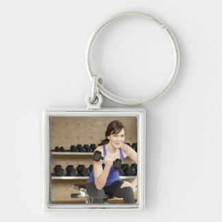 An active female lifting weights in a private keychains